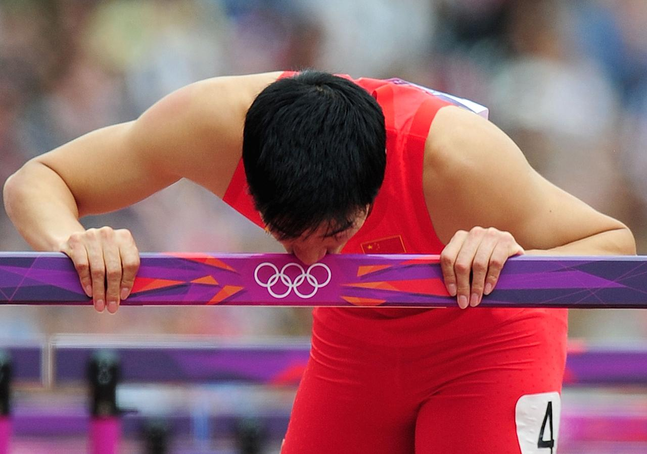 Xiang Liu of China kisses a hurdle after falling in the Men's 110m Hurdles Round 1 Heats on Day 11 of the London 2012 Olympic Games at Olympic Stadium on August 7, 2012 in London, England.  (Photo by Stu Forster/Getty Images)
