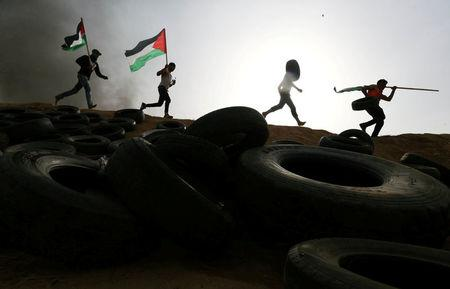 Palestinian protesters run during clashes with Israeli troops at Israel-Gaza border, in the southern Gaza Strip April 5, 2018. REUTERS/Ibraheem Abu Mustafa