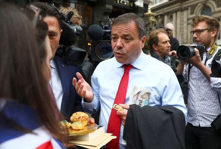 FILE PHOTO:  Arron Banks and Andy Wigmore, who ran the Leave.Eu pro-Brexit referendum campaign, eat pork pies offered by an anti-Brexit campaigner as they arrive to give evidence to the Digital Culture Media and Sport Parliamentary Committee in London
