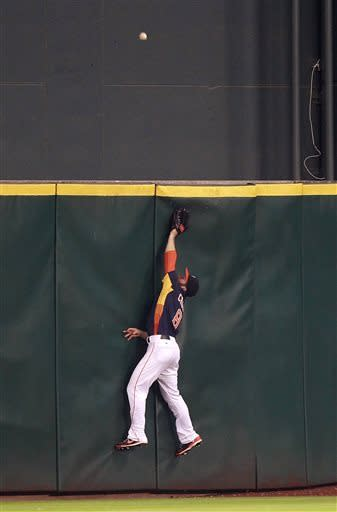 Houston Astros center fielder Trevor Crowe (8) makes a futile leap for Oakland Athletics' Nate Freiman solo home run in the sixth inning during the MLB American League baseball game Sunday, May 26, 2013, in Houston. (AP Photo/Patric Schneider)