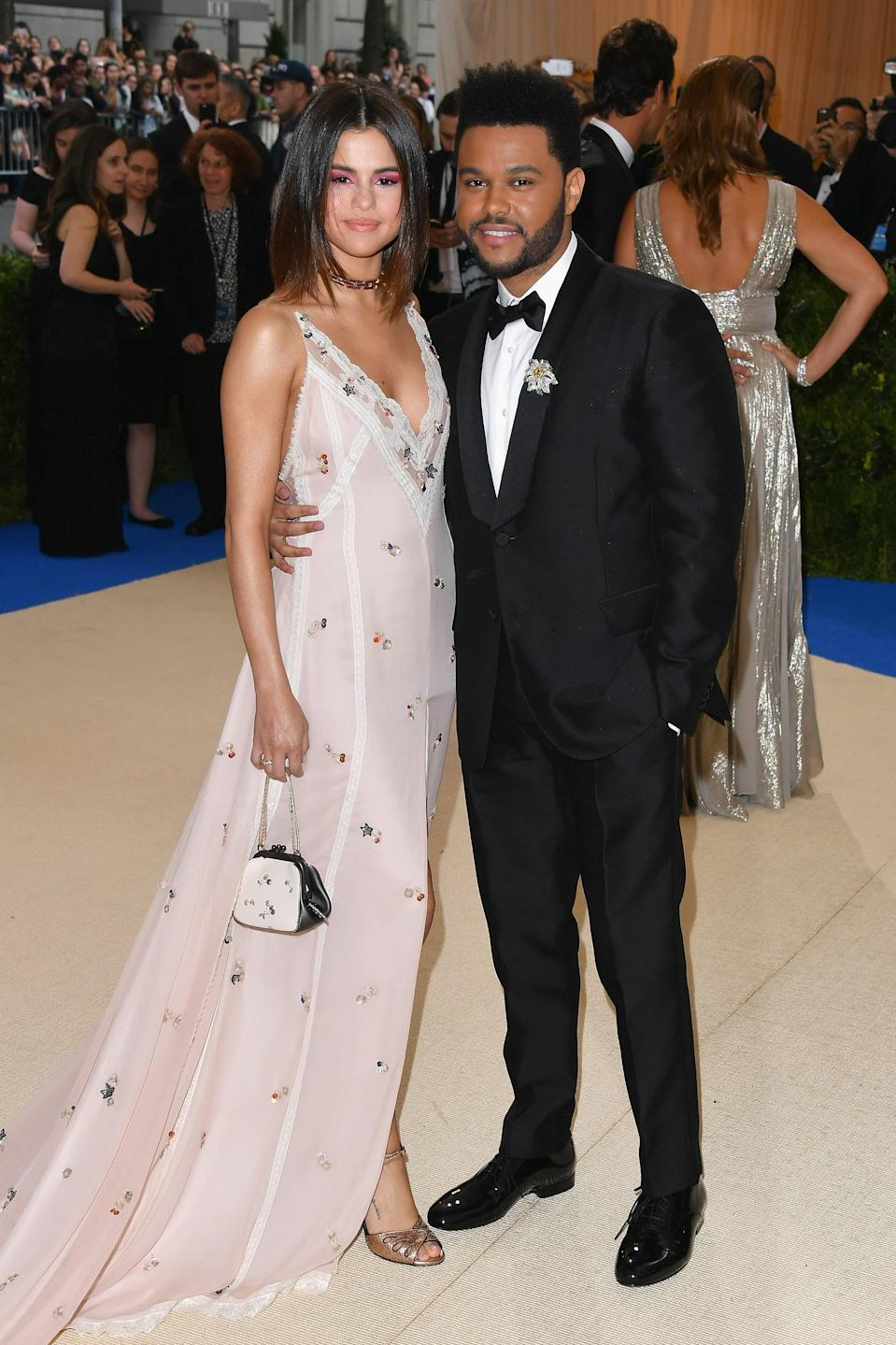 """<h1 class=""""title"""">Selena Gomez in Coach and Tiffany jewelry and The Weeknd in a Valentino tuxedo</h1> <cite class=""""credit"""">Photo: Getty Images</cite>"""
