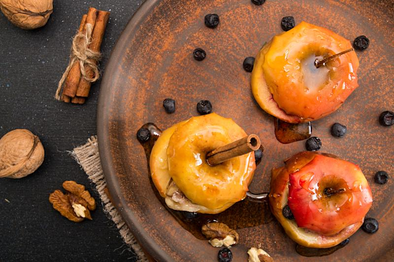 Baked apples stuffed with walnuts and honey on brown plate over on black background. Healthy delicious sweet dessert recipe. Top view. View from above