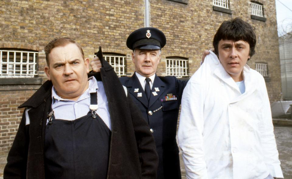 """Old lag Fletcher (Ronnie Barker), fellow prisoner Godber (Richard Beckinsale) and prison officer Mackay (Fulton Mackay) during location shooting for the film version of their TV series """"Porridge"""" at Chelmsford Jail, which has been empty since a fire last year.   (Photo by PA Images via Getty Images)"""