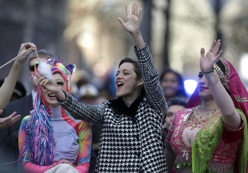 Actress Marion Cotillard, of France, center, the Hasty Pudding Woman of the Year, waves to the crowd as Harvard University theatrical students Renee Rober, left, and Ben Moss, right, ride with her in the back of a convertible during a parade through Harvard Square, in Cambridge, Mass., Thursday, Jan. 31, 2013. The award was presented to Cotillard by Hasty Pudding Theatricals, a theatrical student society at Harvard University. (AP Photo/Steven Senne)