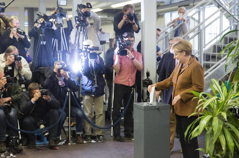 German Chancellor Angela Merkel, chairwoman of the Christian Democratic party CDU, left, casts her vote in Berlin, Sunday, Sept. 22, 2013. 62 million voters in Germany are entitled to elect a new parliament as Merkel runs for her third term as chancellor. (AP Photo/Gero Breloer)