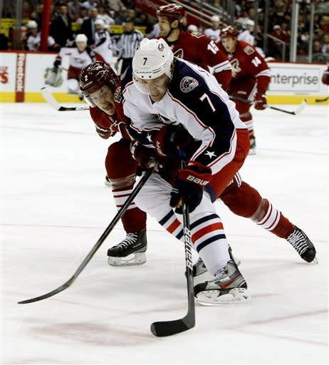 Columbus Blue Jackets defenseman Jack Johnson, right, shoots in front of Phoenix Coyotes defenseman David Rundblad in the first period during an NHL hockey game on Saturday, March 3, 2012, in Glendale, Ariz. (AP Photo/Rick Scuteri)