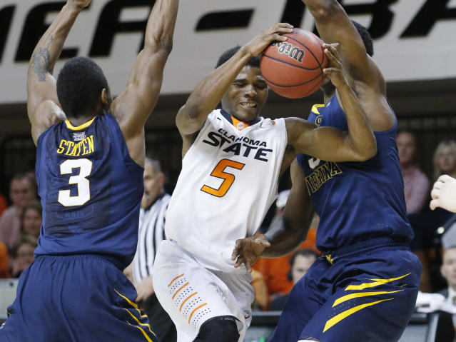Oklahoma State guard Stevie Clark (5) drives between West Virginia guard Juwan Staten (3) and forward Devin Williams (5) in the second half of an NCAA college basketball game in Stillwater, Okla., Saturday, Jan. 25, 2014. Oklahoma State won 81-75.(AP Photo/Sue Ogrocki)