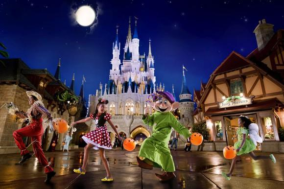 A person in a Dopey costume, a girl in a Minnie Mouse dress, and two other people skipping with the Magic Kingdom castle in the background.