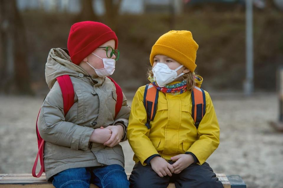 Child boy and girl playing outdoors with face mask protection. School boy breathing through medical mask