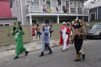Revelers dressed in costumes walk past decorated homes on Mardi Gras Day in the Bywater section of New Orleans, Tuesday, Feb. 16, 2021. Mardi Gras has arrived in New Orleans. But between cold weather and COVID-19, morning streets were nearly empty rather than jam-packed with picnickers and parade watchers. (AP Photo/Gerald Herbert)