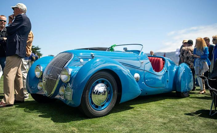 """<p>This cheeky number was built by Emile Darl'mat, a Parisian Peugeot dealer, using a standard 2.0-liter Peugeot 302 chassis. The 1930s were the heyday for art deco cars and their flowing, exaggerated lines and fenders that seemed to trail off to infinity. Talbot-Lago, Delahaye, and Bugatti built the most famous and valuable of the art deco cars, but this roadster, of which 53 were built, has a quirkier style than those thoroughbreds. There are six large chrome discs mounted to each the side of the hood and a massive, nearly heart-shaped badge on the tapered rear that reads """"Darl'mat."""" If you took a long, sweeping Delahaye and mated it to, say, a car that Roger Rabbit might drive, this is most likely what you'd end up with.<em>–Daniel Pund</em></p>"""