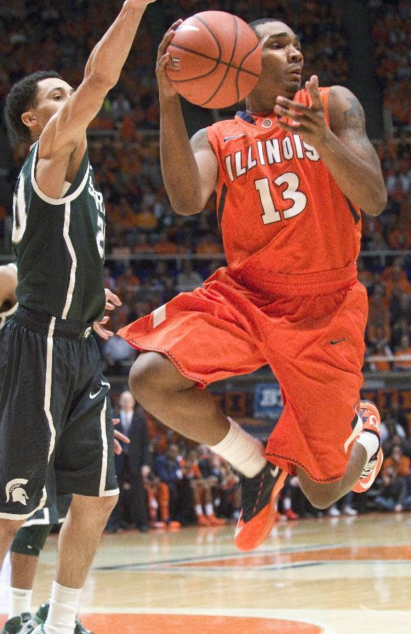 Illinois' Tracy Abrams (13) looks to get rid of the ball next to Michigan State's Travis Trice during an NCAA college basketball game in Champaign, Ill., on Saturday, Jan. 18, 2014. (AP Photo/Robin Scholz)