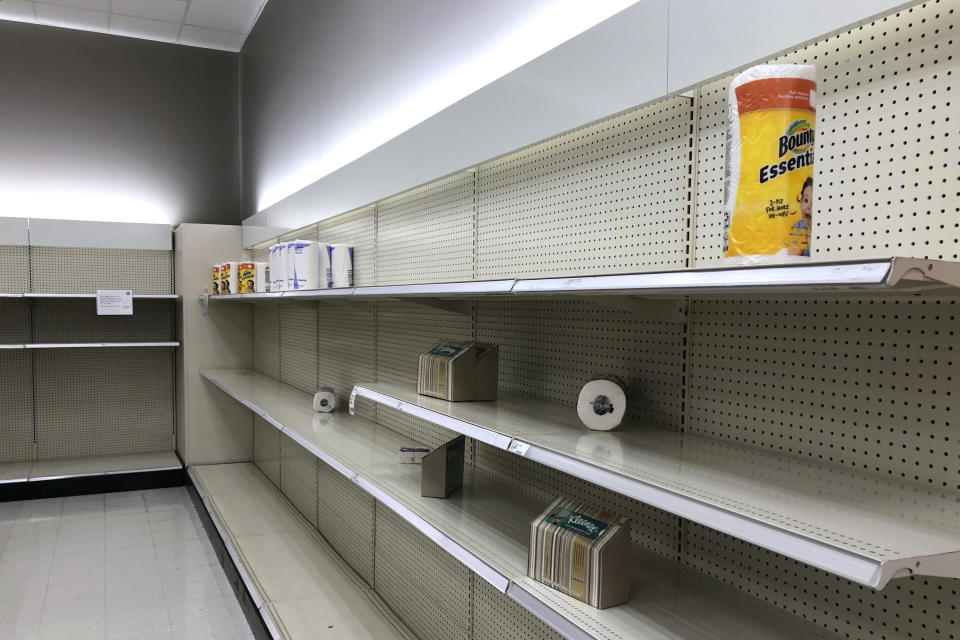 Nearly empty shelves, that usually hold toilet paper, facial tissue and paper towels, are viewed March 14, 2020, in a Target store in Lacey, Wash. (AP Photo/Ted S. Warren)