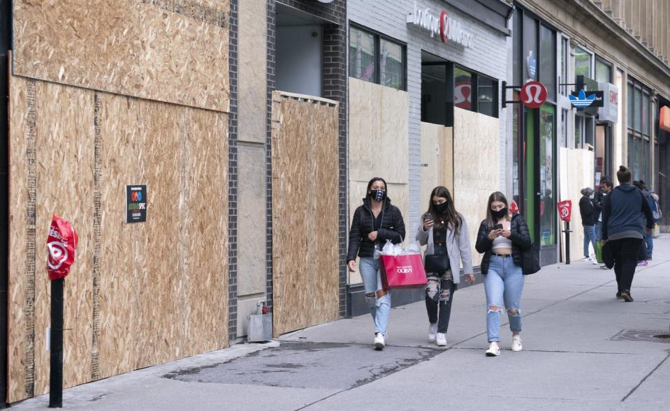 People walk past boarded-up storefront