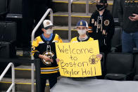 Fans welcome Boston Bruins left wing Taylor Hall, who was acquired in a trade with the Buffalo Sabres, before an NHL hockey game between the Bruins and the Sabres on Tuesday, April 13, 2021, in Boston. (AP Photo/Charles Krupa)