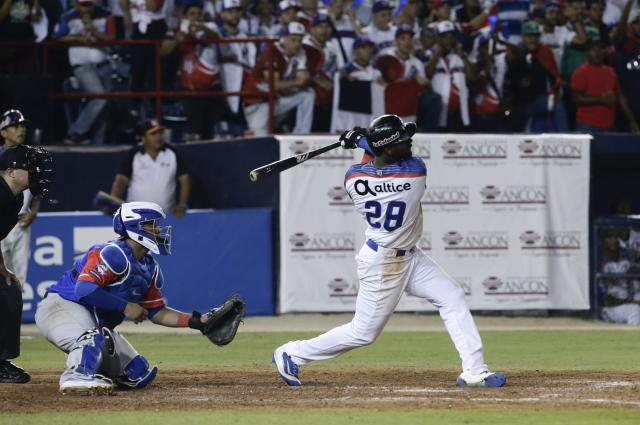 Junior Lake of the Dominican Republic's Estrellas Orientales bats a home run to win against of Puerto Rico's, Cangrejeros de Santurce during the ninth inning on their Caribbean Series baseball tournament match at Rod Carew stadium in Panama City, Thursday, Feb. 7, 2019. (AP Photo/Arnulfo Franco)