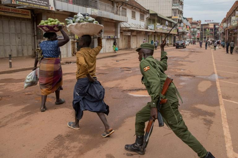 A policeman in the Ugandan capital Kampala beats an orange hawker for defying stay-at-home instructions