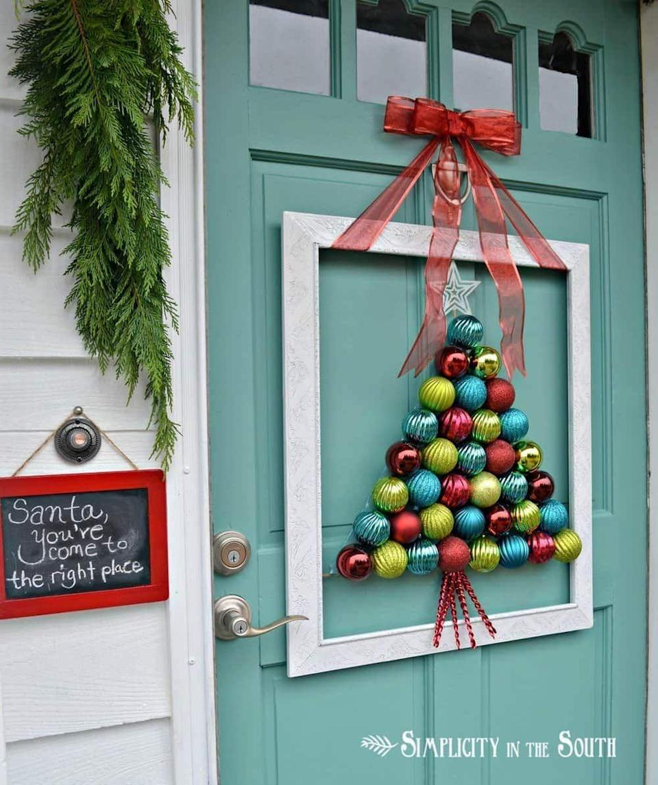 """<p>Add a festive focal point to your holiday porch with an artfully upcycled frame from the dollar store or thrift shop. In the center, place a wreath, welcome sign, or any other holiday flair.<br></p><p><strong><em>Get the look at <a href=""""https://www.simplicityinthesouth.com/framed-christmas-tree-ornament-wreath"""" rel=""""nofollow noopener"""" target=""""_blank"""" data-ylk=""""slk:Simplicity in the South"""" class=""""link rapid-noclick-resp"""">Simplicity in the South</a>.</em></strong> </p>"""