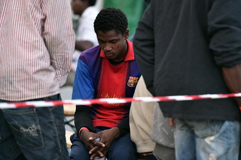 Migrants wait to be identified by police after arriving in Italy's Palermo (AFP Photo/Gabriel Bouys)