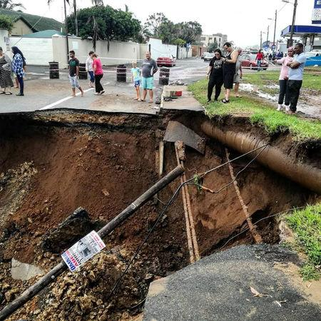 People stand on a damaged road after massive flooding in Amanzimtoti, near Durban, South Africa April 23, 2019 in this picture obtained from social media on April 24, 2019. Gavin Welsh via REUTERS