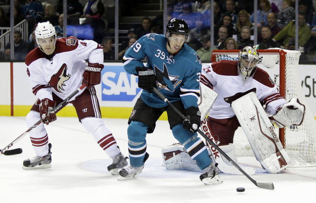 San Jose Sharks' Logan Couture, center, controls the puck next to Phoenix Coyotes goalie Mike Smith, left, and Zbynek Michalek (4), of the Czech Republic, during the first period of an NHL hockey game on Saturday, Nov. 2, 2013, in San Jose, Calif. (AP Photo/Marcio Jose Sanchez)