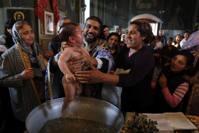 Priest Nicolae Ganga (C), a member of Romania's Roma ethnic minority, baptizes a child during a very rare mass Orthodox baptism ceremony at a church in the Bora neighbourhood in Slobozia, 130 km (81 miles) east of Bucharest November 29, 2012. About 40 Roma ethnic people, aged between one and 57 years, were baptized into the Orthodox Christian faith with Romanians serving as godparents during a very rare mass ceremony in an attempt to strengthen their community ties with the Romanian majority. The Roma people make up the biggest ethnic minority in the European Union, most of them from countries like Romania, Bulgaria and the Czech Republic. There are an estimated 10 million across Europe and one in five lives in Romania. REUTERS/Bogdan Cristel (ROMANIA - Tags: SOCIETY RELIGION TPX IMAGES OF THE DAY) TEMPLATE OUT