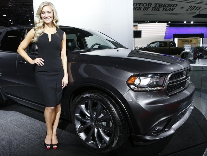 Model poses next to a 2014 Dodge Durango during the press preview day of the North American International Auto Show in Detroit