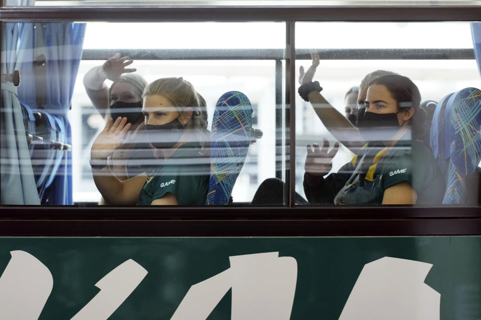 Members of Australia's Olympic softball squad wave to media from their bus upon arrival at Narita international airport, Tuesday, June 1, 2021, in Narita, east of Tokyo. Australia's Olympic softball squad touched down in Japan on Tuesday and was among the earliest arrivals for the Tokyo Games.(AP Photo/Eugene Hoshiko, Pool)