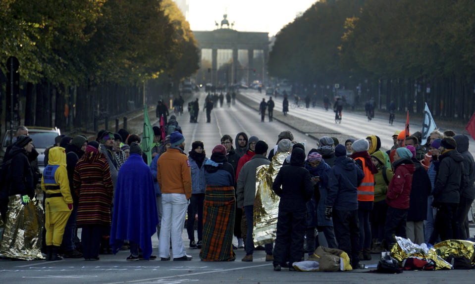 Supporters of the 'Extinction Rebellion' movement block a road between the Brandenburg Gate, background, and the Victory Column in Berlin, Germany, Monday, Oct. 7, 2019. The activists want to draw attention on the climate protest by blocking roads and with other acts of civil disobedience in Berlin and other cities around the world. (AP Photo/Michael Sohn)