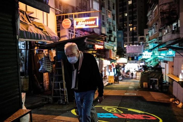 """A man wears a face mask as he walks along a street popular for its restaurants and bars in Hong Kong after the city's chief executive announced plans to temporarily ban the sale of alcohol to help stop the spread of the coronavirus. <span class=""""copyright"""">(Anthony Wallace / AFP / Getty Images)</span>"""