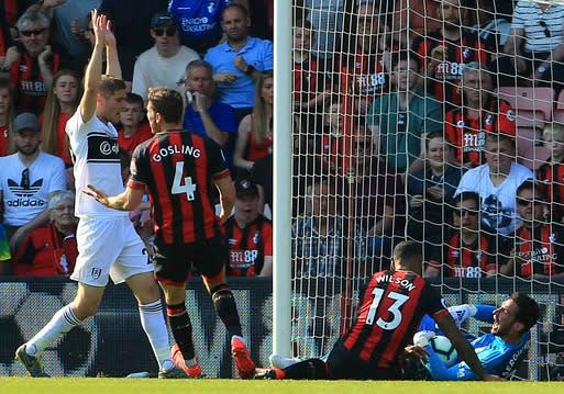 Bournemouth's Callum Wilson and Fulham goalkeeper Sergio Rico battle for the ball during the English Premier League soccer match between Bournemouth and Fulham at the Vitality Stadium, Bournemouth England. Saturday, April 20, 2019. (Mark Kerton/PA via AP)
