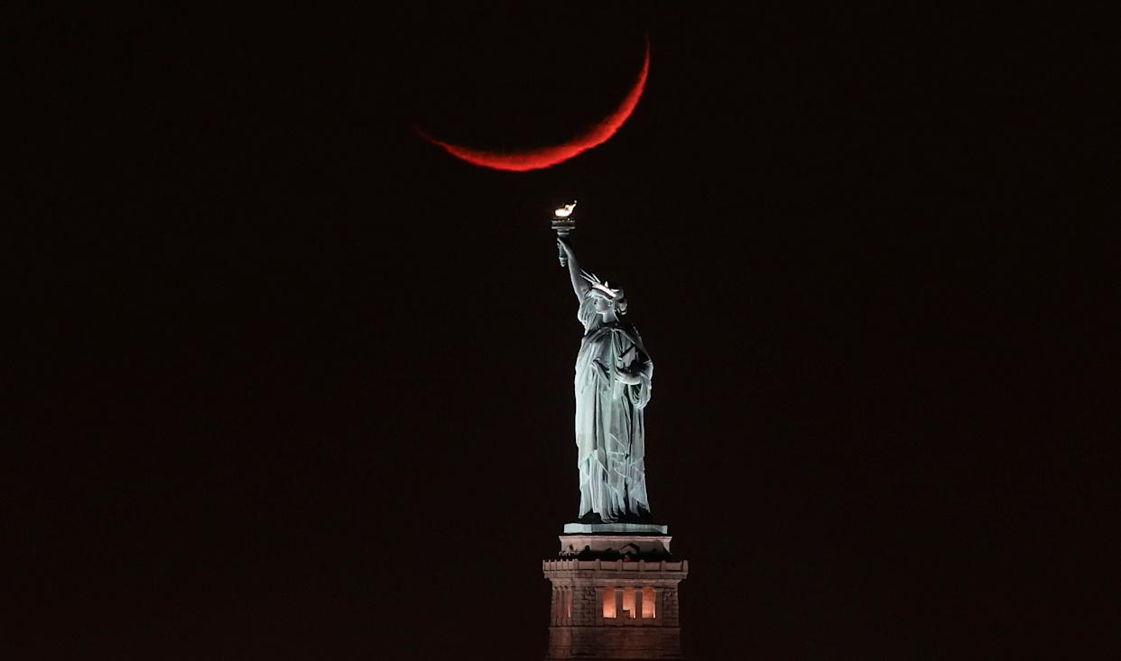 A crescent moon sets behind the Statue of Liberty on Jan. 19, 2018 in New York City. (Photo: Gary Hershorn via Getty Images)