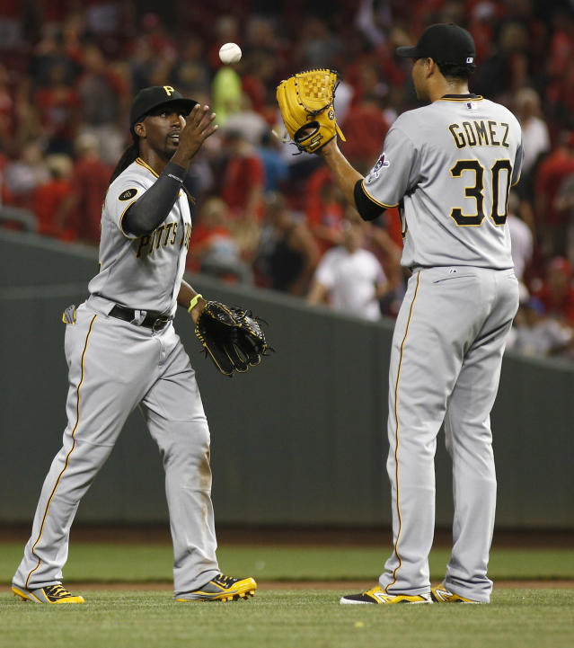 Pittsburgh Pirates' Andrew McCutchen, left, throws the ball to relief pitcher Jeanmar Gomez after the Pirates defeated the Cincinnati Reds 6-5 in 11 innings in a baseball game, Saturday, July 12, 2014, in Cincinnati. (AP Photo/David Kohl)