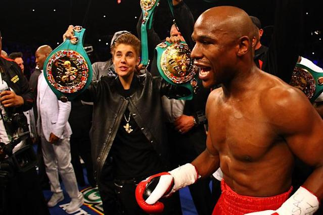 LAS VEGAS, NV - MAY 05: (L) Singer Justin Bieber holds up a belt for Floyd Mayweather Jr. before Mayweather Jr. takes on Miguel Cotto during their WBA super welterweight title fight at the MGM Grand Garden Arena on May 5, 2012 in Las Vegas, Nevada. (Photo by Al Bello/Getty Images)