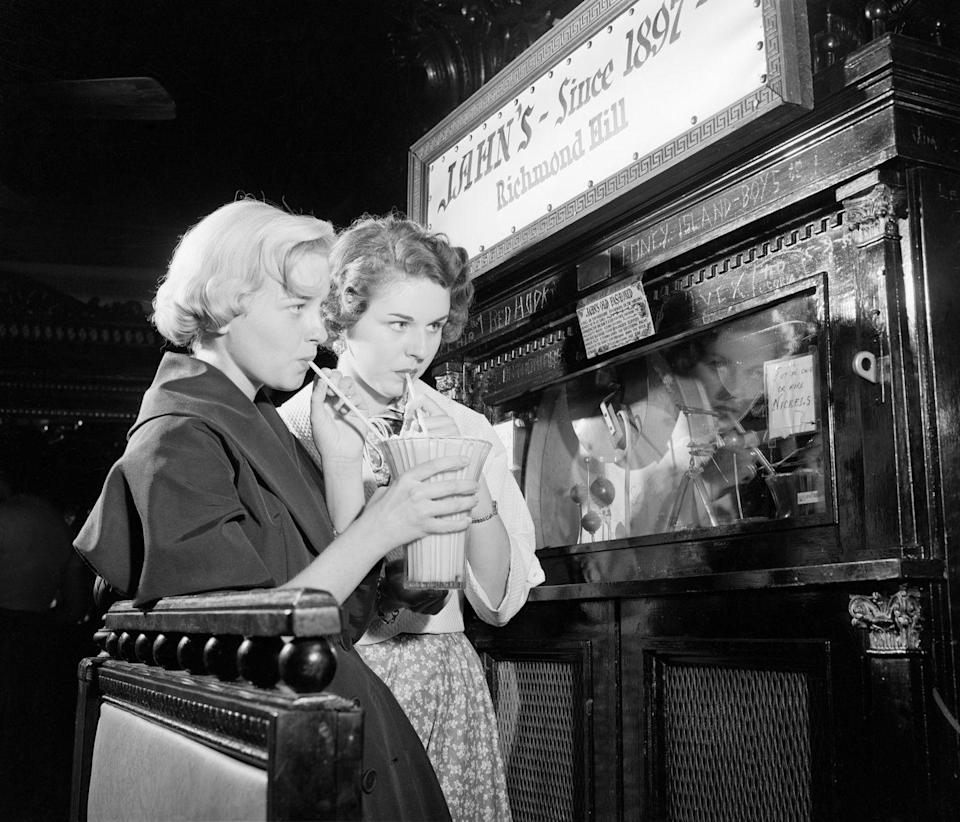 """<p>At Jahn's Ice Cream Shop in New York City, two young ladies share the shop's signature """"largest ice cream soda in the world."""" </p>"""
