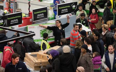 Customers surrounded by shelves on Black Friday in Asda - Credit: Simon Dawson/Bloomberg News