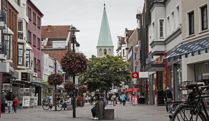 Only a few people walk on the shopping street in the center of Hamm, Germany, Monday, Sept. 28, 2020. The city of Hamm is the number one corona hotspot at the moment in Germany, with a sudden increase of Covid-19 infections. Most of them are related to a wedding with more than 300 guests. (AP Photo/Martin Meissner)