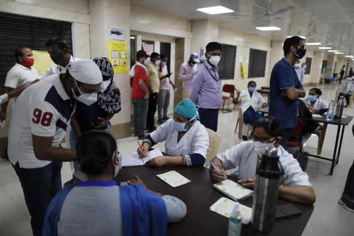 Indians register themselves to receive the vaccine for COVID-19 at a medical college in Prayagraj, India, Saturday, May 8, 2021. Two southern states in India became the latest to declare lockdowns, as coronavirus cases surge at breakneck speed across the country and pressure mounts on Prime Minister Narendra Modi's government to implement a nationwide shutdown. (AP Photo/Rajesh Kumar Singh)