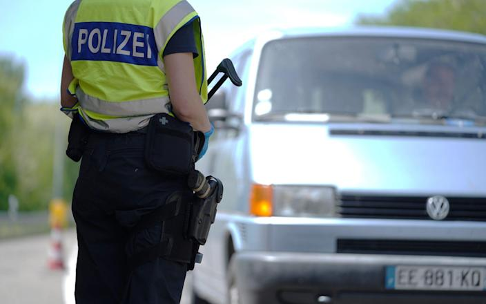 RASTATT, GERMANY - MAY 08: A German border police officer stops cars in a checkpoint of the D87 road at the German-French border during the coronavirus crisis on May 8, 2020 near Rastatt, Germany. The rates of new infections in both Germany and France, as in much of the European Union, have fallen dramatically over recent weeks, allowing governments to ease lockdown measures and strengthening demands by both business leaders and local communities to reopen international borders. In Germany so far Interior Minister Horst Seehofer is resisting a fast-paced lifting of border closures. (Photo by Thomas Niedermueller/Getty Images) - Thomas Niedermueller/ Getty Images Europe