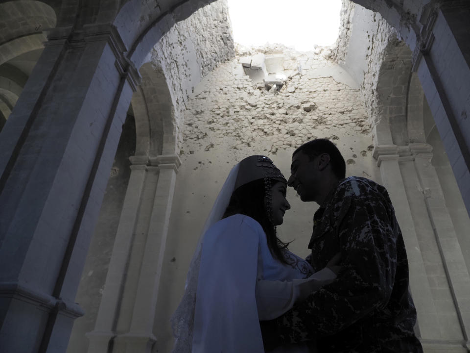 Newlyweds, soldier Hovhannes Hovsepyan, right, and Mariam Sargsyan hug after their wedding ceremony in the Holy Savior Cathedral, damaged by shelling by Azerbaijan's artillery during a military conflict in Shushi, the separatist region of Nagorno-Karabakh, Saturday, Oct. 24, 2020. The wedding was celebrated even as intense fighting in the region has continued. (AP Photo)
