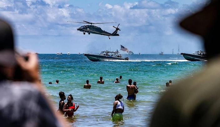 Beach goers watch a helicopter and vessels with the Air and Marine Operations performing during The National Salute to Americas Heroes Air and Sea Show presented by Hyundai in Miami Beach. on Saturday, May 29, 2021.