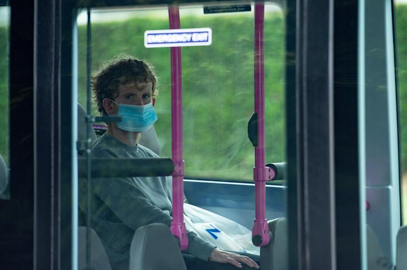 A person wearing a protective face covering boards a bus on Bowhill Grove in Leicester, where the localised lockdown boundary cuts through. A local lockdown has been imposed following a spike in coronavirus cases in the city.