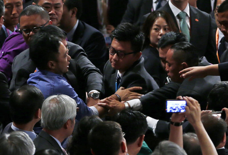 "A protester, center left, is ushered away by security officials after he shouted ""(for China) To reverse its condemnation of the brutal June 4, 1989 crackdown on protesters in Tiananmen Square and to end to one-party rule in China "" before Chinese President Hu Jintao's address after Hong Kong's new Chief Executive Leung Chun-ying was sworn in at the Hong Kong Convention and Exhibition Center Sunday, July 1, 2012. Hong Kong's new Beijing-backed leader was sworn in on Sunday amid a rising tide of public discontent over widening inequality and lack of full democracy in the semiautonomous southern Chinese financial center. (AP Photo/Vincent Yu)"