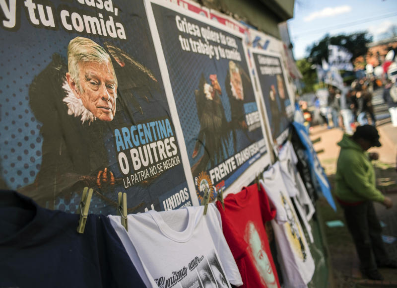 """A man sells t-shirts next to banners depicting US judge Thomas Griesa outside the Luna Park stadium during a ceremony against the so called """"vulture funds"""", in Buenos Aires on August 12, 2014 (AFP Photo/Leo La Valle)"""