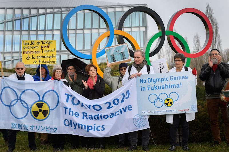 Activists stage a protest in front of the headquarters of the International Olympic Committee (IOC) against the holding of the Tokyo 2020 Olympic Games on Feb. 26. (Photo by Fabrice COFFRINI/AFP)