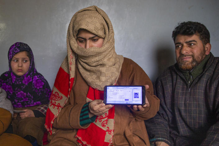 "Zarqa Mushtaq, center, shows on a mobile phone the 11th grade examination slip of her 16 -year old brother Athar Mushtaq, as her father Mushtaq Ahmad Wani, looks on while talking to the Associated Press in Bellow, south of Srinagar, Indian controlled Kashmir, Tuesday, Jan. 5, 2021. On the last week of 2020, Indian government forces killed Athar and two other young men during a controversial gunfight on the outskirts of the Indian-controlled Kashmir's main city. Police did not call them anti-India militants but ""hardcore associates of terrorists."" They later buried them at a graveyard in a remote mountainous tourist resort miles away from their ancestral villages. Athar was the latest Kashmiri to be buried in a far-off graveyard after Indian authorities in a new controversial policy in 2020 started to consign blood-soaked bodies of scores of Kashmiri suspected rebels to unmarked graves, denying the mourning families a proper funeral and a burial. (AP Photo/ Dar Yasin)"