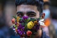 A person smiles as he wears a face mask amid of new coronavirus pandemic during the Diversity parade in Montevideo, Uruguay, Friday, Sept. 25, 2020. The event is held every year to raise awareness and fight against discrimination based on sexual identity and orientation. (AP Photo/Matilde Campodonico)