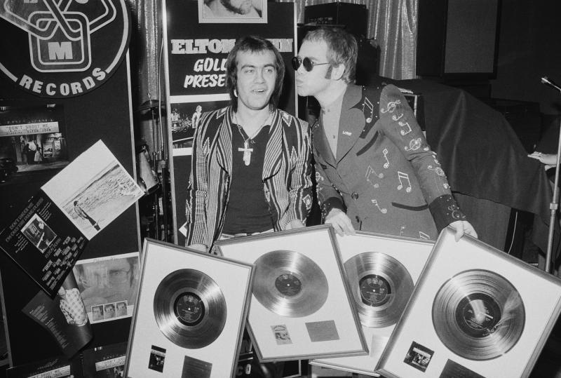 Bernie Taupin and Elton John at a 1973 ceremony to award them gold discs for four of their co-written albums. (Photo: Michael Putland/Getty Images)