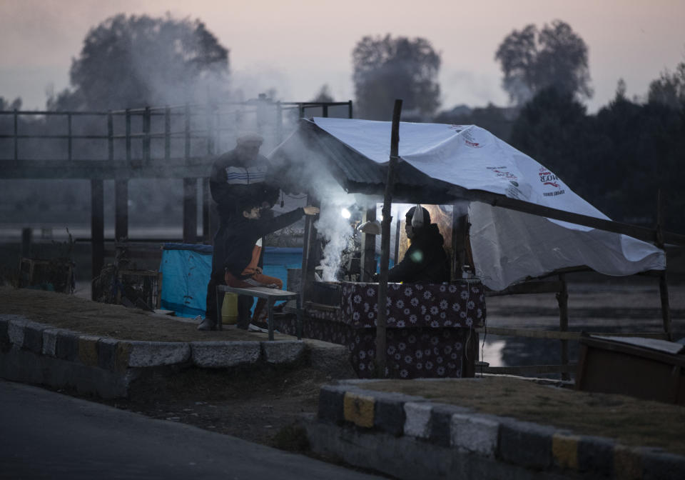 A Kashmiri vendor prepares traditional barbeque mutton for customers on the bank of the Dal Lake on a cold evening in Srinagar on Nov. 16, 2020. (AP Photo/Mukhtar Khan)