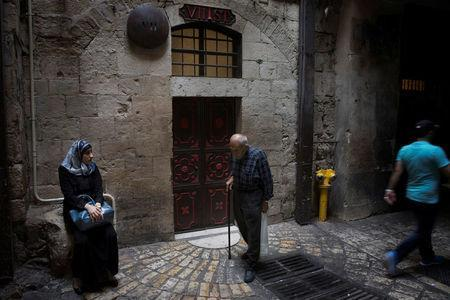 FILE PHOTO: People pass by the seventh station of the cross on Via Dolorosa, or the Way of the Cross, believed by Christians to be the route Jesus Christ carried his cross to his crucifixion, in Jerusalem's Old City May 20, 2014. REUTERS/Finbarr O'Reilly/File Photo